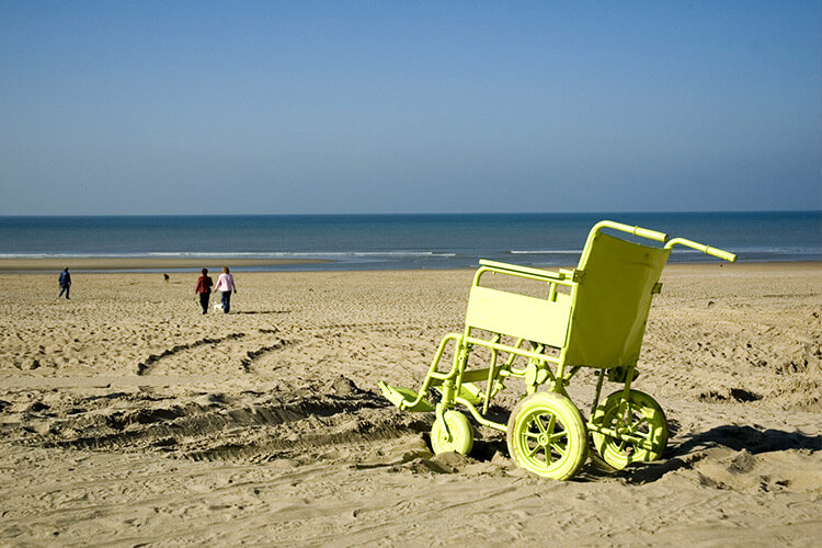 Yellow beach wheelchair in front of the sea