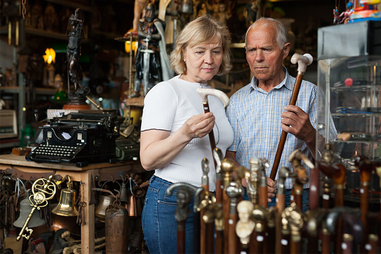 Man and Woman Curiously Looking At Walking Sticks and Canes