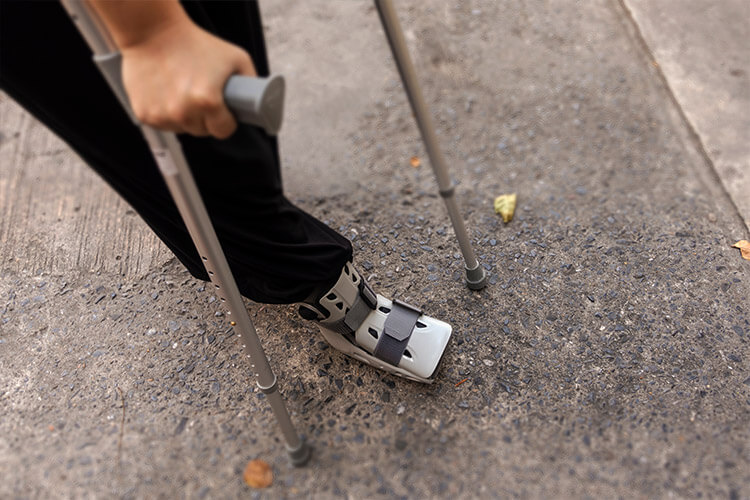 Person Using Crutches with a Walking Boot