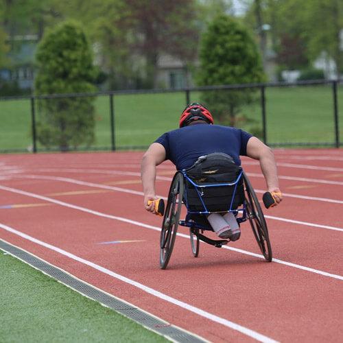 Man Racing Sports Wheelchair on Track